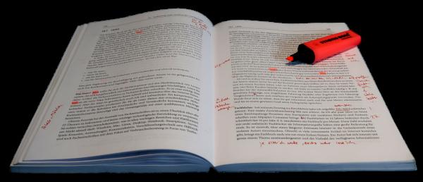 Aufgeschlagenes Buch mit rotem Textmarker
